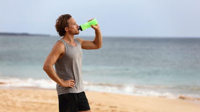 Fitness runner man drinking water