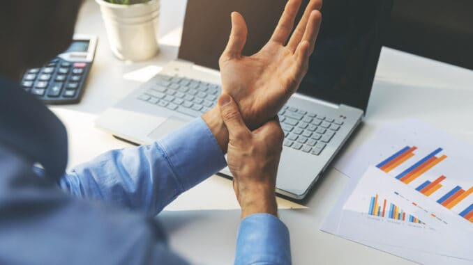 man suffering from wrist joint pain while working on laptop