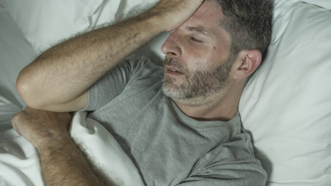 Dramatic portrait of stressed and frustrated man in bed