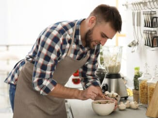 Young man cooking tasty cream soup with mushrooms