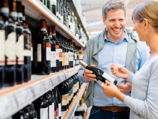 Woman and man buying red wine in supermarket