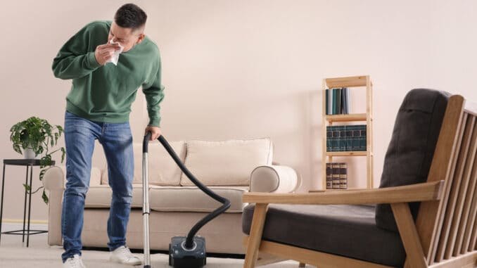 Man with dust allergy cleaning his home