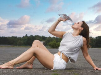Young woman in shorts sitting on pavement and drinking wate