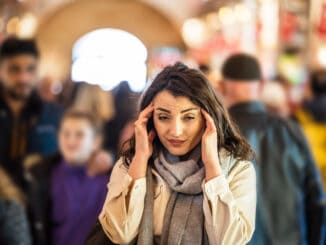 Beautiful woman in fashionable modern clothes suffers migraine or headache problem while standing crowd of people at road