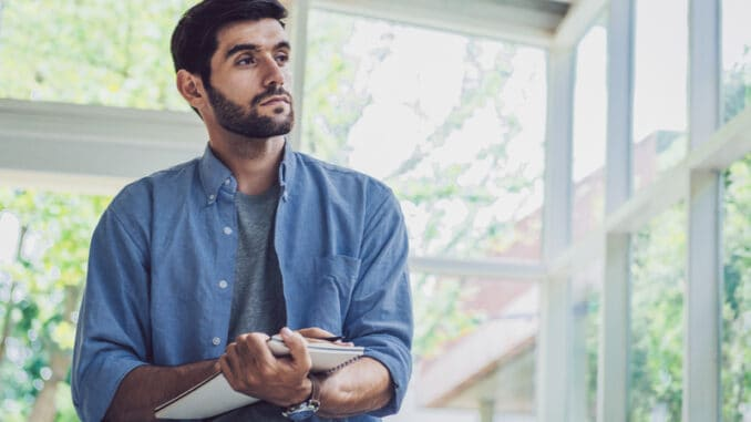 A man looking and thinking at note book while working at home office