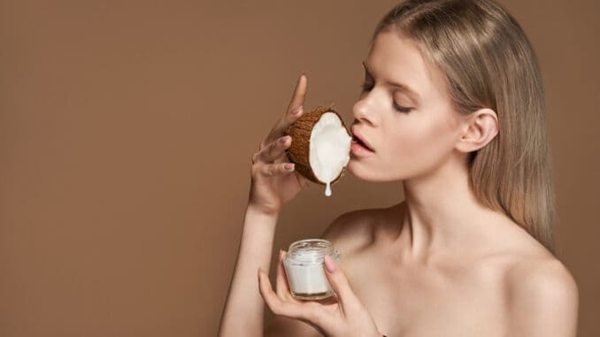 Beautiful young adult woman hold coconut in hand