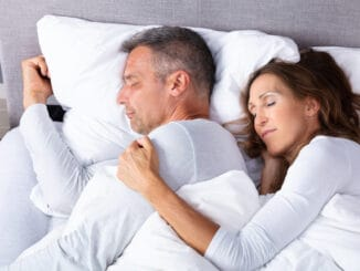 Mature Loving Couple Sleeping On Bed With White Blanket