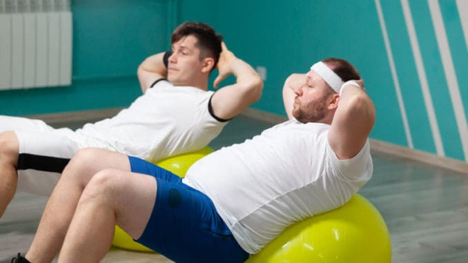 Tired fat man is lying on a fitness ball training during group fitness classes.