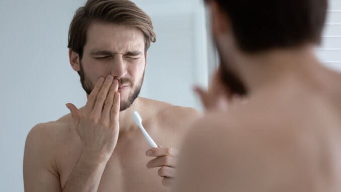 Young caucasian man wash brush teeth in bathroom have painful feeling suffer from gingivitis or periodontitis, millennial male struggle with oral dental problems, gums bleeding or inflammation