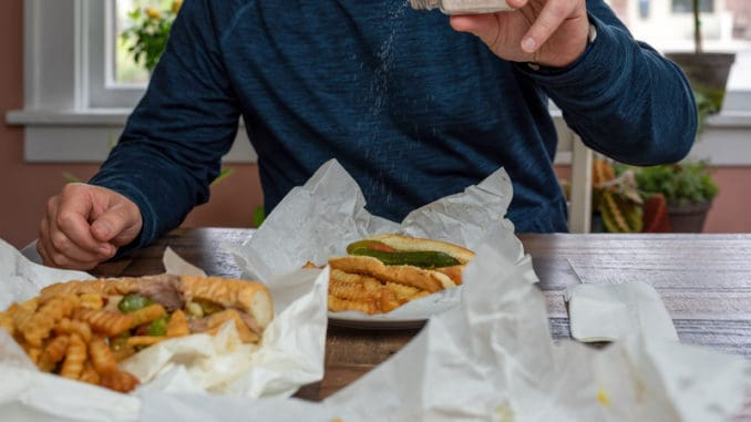 Supporting local restaurants by ordering takeout for lunch - a man is adding salt to his french fries