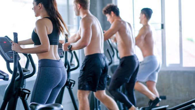 Beautiful sport women exercise with elliptical machine among the other men in the gym with day light.