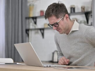 The Young Man with Spinal Back Pain Working on Laptop