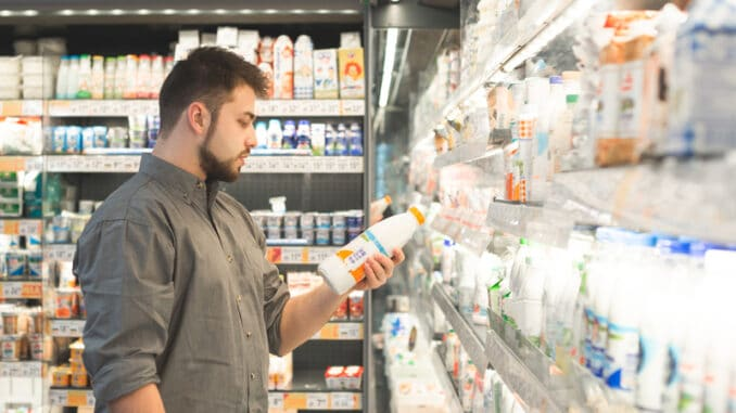 Man is in the milk department of a supermarket