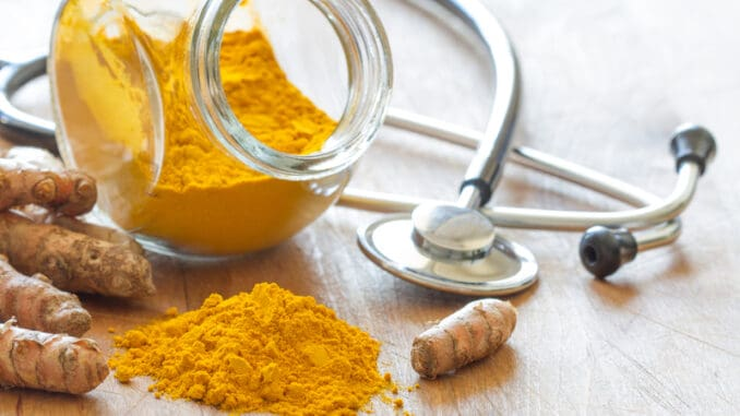 Turmeric powder and turmeric roots with stethoscope, natural medicine concept