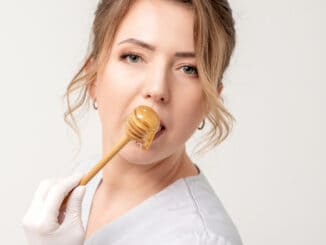 Portrait of beautiful young caucasian woman eating honey with wooden spoon on white background