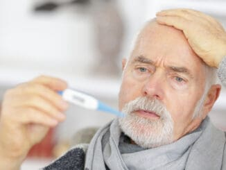 Senior man checking body temperature with thermometer