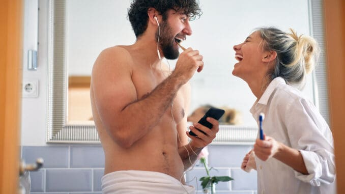 Sweet couple brushing teeth together in the morning