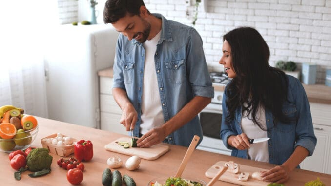 Couple preparing dinner together on home kitchen.