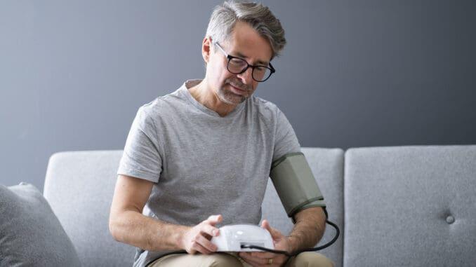 Elder Man Checking Blood Pressure At Home