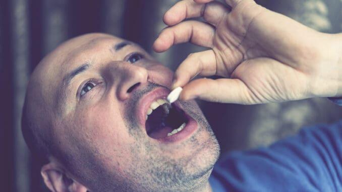 Extreme closeup man face taking white pill