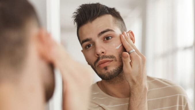 Portrait of young man applying face cream while looking in mirror during morning skincare routine