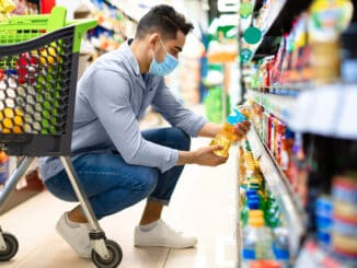 Middle-Eastern Man Doing Grocery Shopping Choosing Cooking Oil On Shelf In Supermarket.