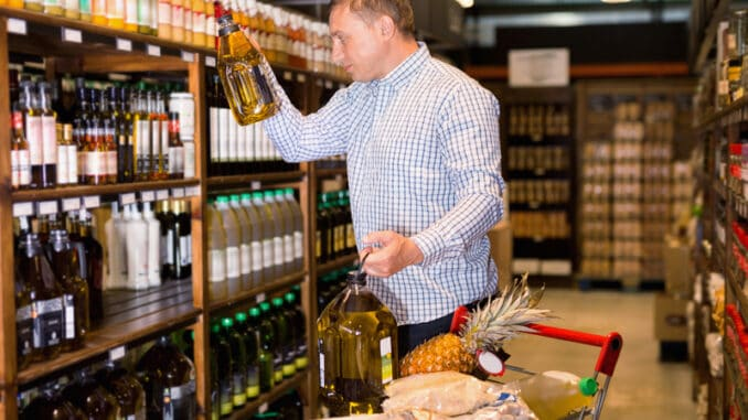 Portrait of glad cheerful positive man buying olive oil in supermarket