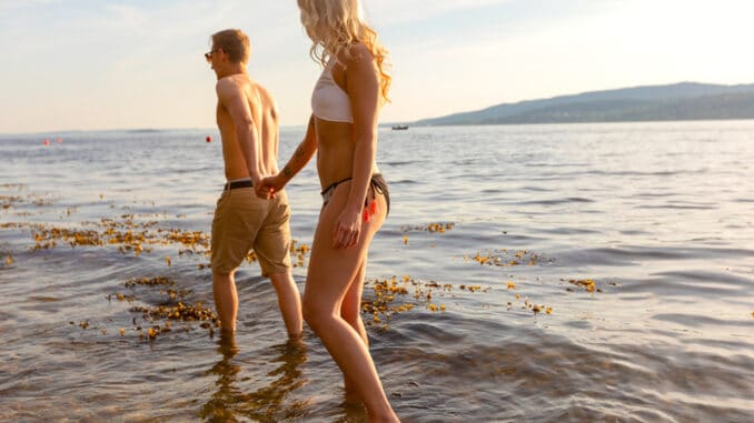 Romantic couple holding hands and wading in the sea shore in the evening.