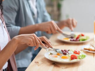 Unrecognizable couple using fork and knife while eating tasty breakfast in kitchen