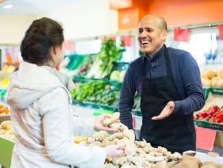 friendly salesman helping female customer to choose ginger in supermarket