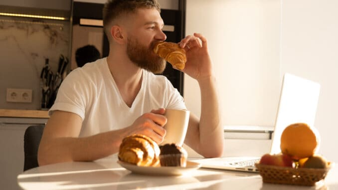 Young man eating croissant and drinking tea or coffee on breakfast
