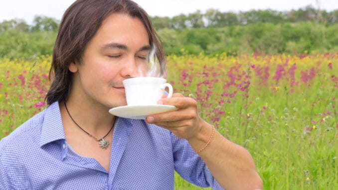 Portrait of young happy smiling man drinking coffee or tea outdoors