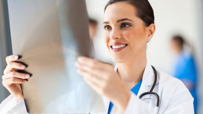 Happy medical doctor looking at x-ray film
