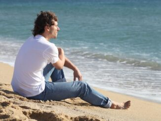 Man thinking and watching the sea on the beach
