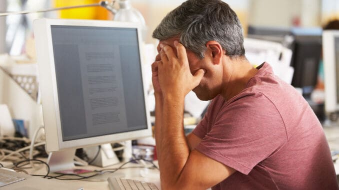 Stressed Man Working At Desk In Busy Creative Office On Computer