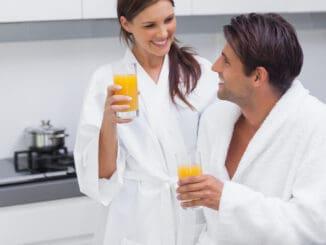 Couple drinking orange juice in the kitchen