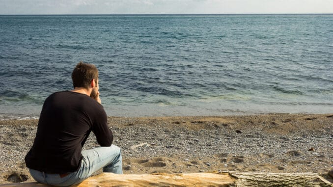 A man sitting on a log looking out to the sea and thinking