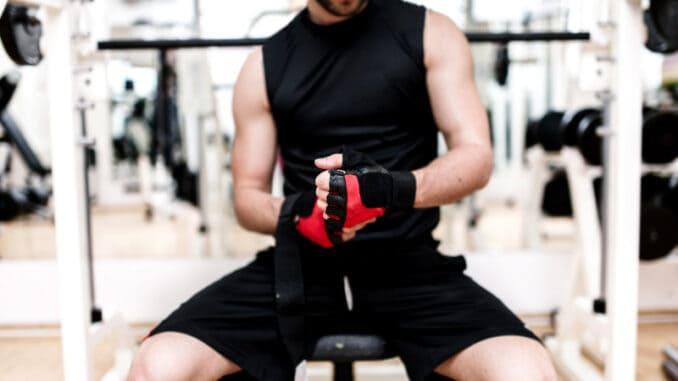 Man at gym preparing for workout, putting gloves on