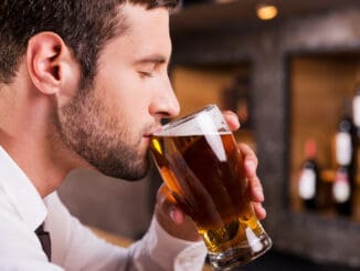 Side view of handsome young man drinking beer while sitting at the bar counter