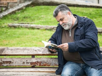 Attractive bearded man reading in a big park