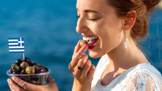 Smiling woman eating fresh green and black olives