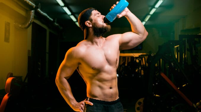 Man in the gym drinking from the shake
