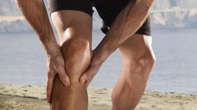 Young sport man with strong athletic legs holding knee with his hands in pain