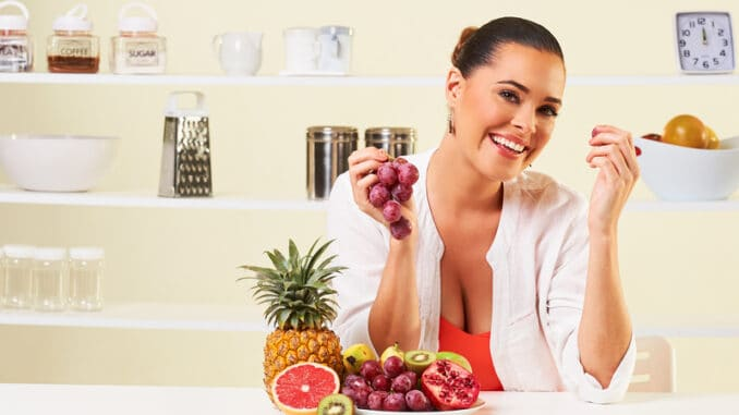 Young beautiful woman eating grapes from a fruit bowl in the kitchen