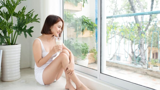 Asian beautiful young woman drinking milk at home.
