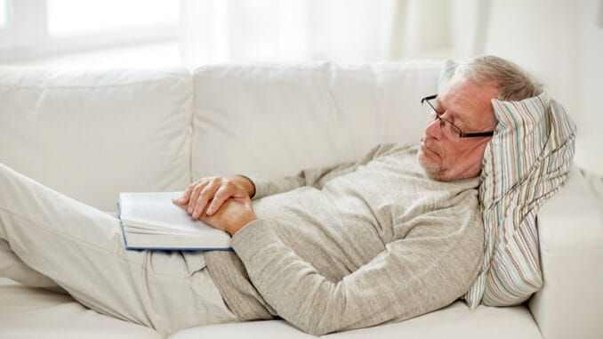 Old age, rest and people concept - senior man lying on sofa with book and sleeping at home
