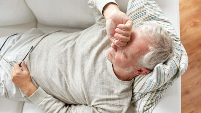 close up of tired senior man lying on sofa at home
