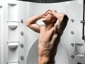 Young strong body man taking a shower to cleanse the body after tired workout and stressed from work in new bathroom with hydro massage bath tub