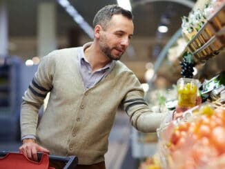 Portrait of smiling handsome man grocery shopping in supermarket