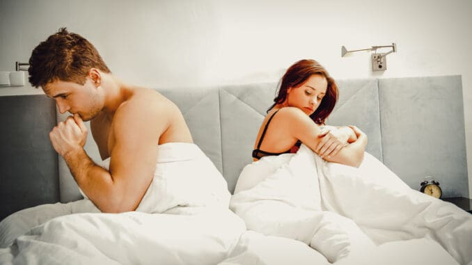 Young lovely couple sitting in bed after argue.